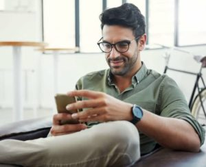 Man Sitting Down and Looking at His Phone