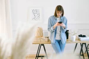 Woman Using Her Mobile Device to Make a Phone Call From Her Home Office